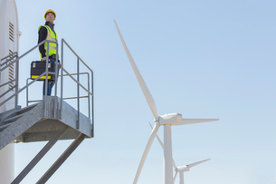 Worker standing on wind turbine in rural landscapeの写真素材 [FYI02154364]
