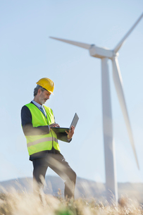 Worker using laptop by wind turbine in rural landscapeの写真素材 [FYI02154394]
