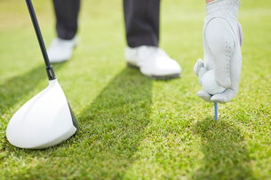 Man teeing golf ball on courseの写真素材 [FYI02154426]