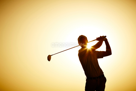 Silhouette of man swinging golf clubの写真素材 [FYI02154490]