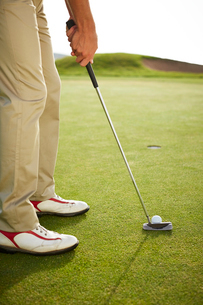 Man preparing to putt on golf courseの写真素材 [FYI02154523]