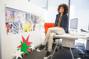 Portrait of smiling businesswoman sitting on deskの写真素材 [FYI02154537]