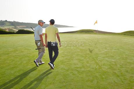 Men walking toward hole on golf course overlooking oceanの写真素材 [FYI02154663]