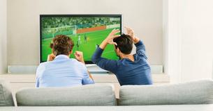 Men watching soccer game on sofaの写真素材 [FYI02154692]