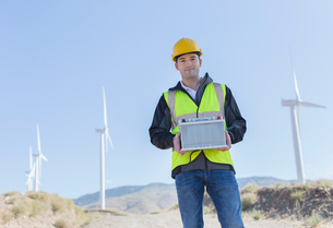 Worker standing by wind turbines in rural landscapeの写真素材 [FYI02154710]