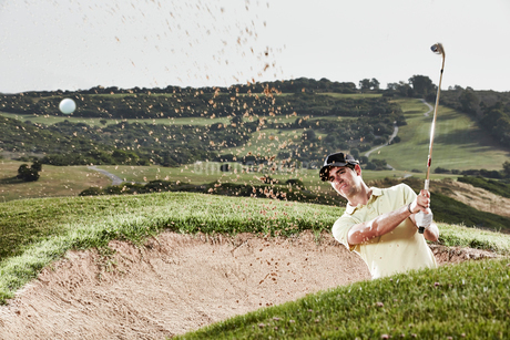 Man swinging from sand trap on golf courseの写真素材 [FYI02154717]