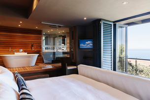 Modern master bedroom and bathroom overlooking oceanの写真素材 [FYI02154837]