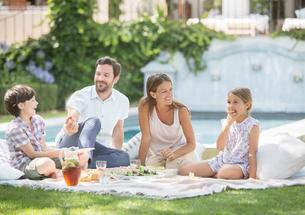 Family enjoying picnic in grassの写真素材 [FYI02154871]