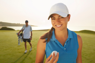 Woman holding golf ball on courseの写真素材 [FYI02154902]