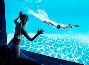 Woman watching boyfriend underwater in swimming poolの写真素材 [FYI02155005]