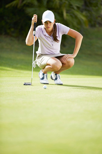 Woman preparing to putt on golf courseの写真素材 [FYI02155035]