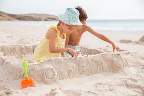 Children making sandcastle on beachの写真素材 [FYI02155062]