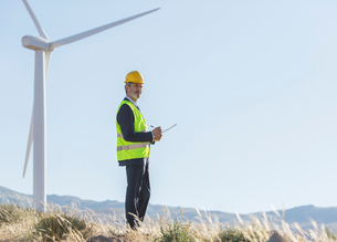 Businessman examining wind turbines in rural landscapeの写真素材 [FYI02155082]