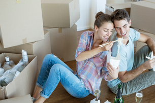 Couple sharing Chinese take out food in new houseの写真素材 [FYI02155157]