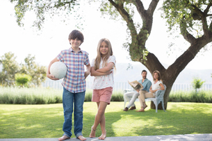 Brother and sister with volleyball in backyardの写真素材 [FYI02155205]