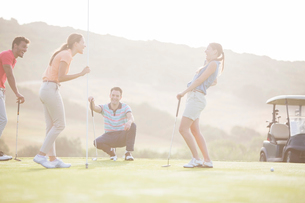 Friends laughing near hole on golf courseの写真素材 [FYI02155209]