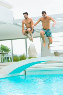 Men jumping into swimming poolの写真素材 [FYI02155301]