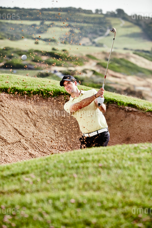 Man swinging from sand trap on golf courseの写真素材 [FYI02155333]