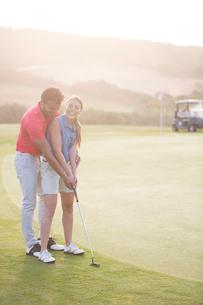 Man teaching woman to golfの写真素材 [FYI02155339]