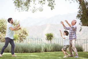 Multi-generation family playing volleyball in backyardの写真素材 [FYI02155364]