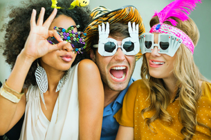Smiling friends wearing decorative glassesの写真素材 [FYI02155418]
