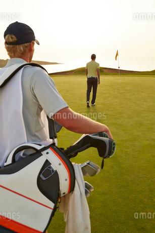 Golfer and caddy nearing golf flagの写真素材 [FYI02155439]