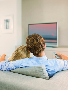 Couple watching television on sofaの写真素材 [FYI02155440]