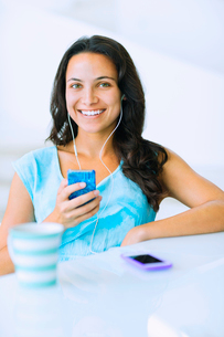 Portrait of smiling woman listening to mp3 player at tableの写真素材 [FYI02155446]