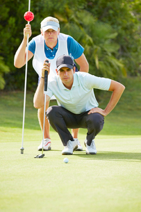 Caddy and golfer on putting greenの写真素材 [FYI02155468]
