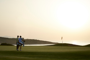 Men on golf course at sunsetの写真素材 [FYI02155538]