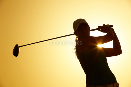Silhouette of woman playing golf on courseの写真素材 [FYI02155617]