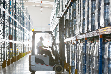 Worker operating forklift in warehouseの写真素材 [FYI02155632]