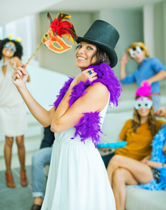 Woman wearing decorative hat with mask at partyの写真素材 [FYI02155648]