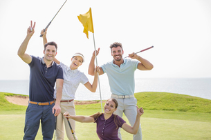 Enthusiastic friends waving on golf courseの写真素材 [FYI02155654]