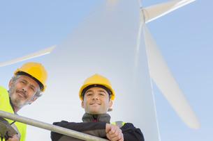 Workers standing on wind turbine in rural landscapeの写真素材 [FYI02155670]