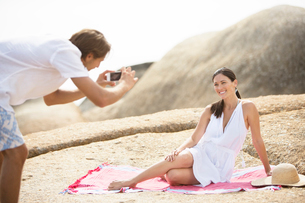 Man taking picture of girlfriend on beachの写真素材 [FYI02155685]
