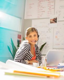 Businesswoman wearing headset at desk in officeの写真素材 [FYI02155689]