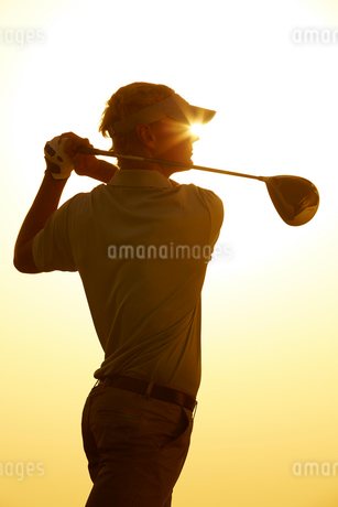 Silhouette of man swinging golf clubの写真素材 [FYI02155709]