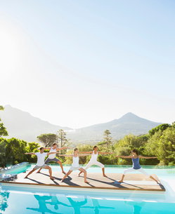 People practicing yoga at poolsideの写真素材 [FYI02155711]
