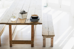 Plates and silverware stacked on wooden tableの写真素材 [FYI02155887]