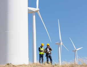 Workers talking by wind turbines in rural landscapeの写真素材 [FYI02155915]