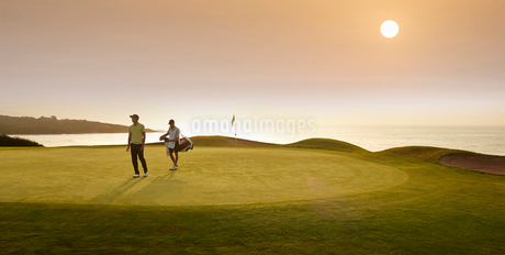Golfer and caddy walking on golf courseの写真素材 [FYI02155919]