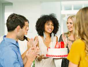 Friends clapping around woman with birthday cakeの写真素材 [FYI02155935]