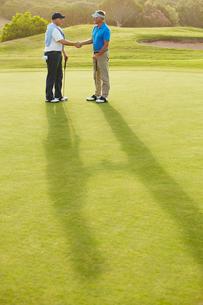 Senior men shaking hands on golf courseの写真素材 [FYI02155976]