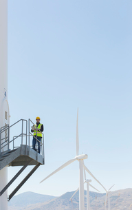 Worker standing on wind turbine in rural landscapeの写真素材 [FYI02155994]