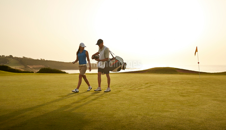 Caddy and woman walking on golf course overlooking oceanの写真素材 [FYI02156028]