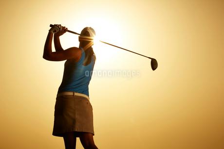 Sun shining behind woman swinging golf clubの写真素材 [FYI02156050]