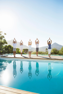 People practicing yoga at poolsideの写真素材 [FYI02156096]