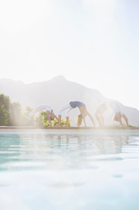 People practicing yoga at poolsideの写真素材 [FYI02156108]