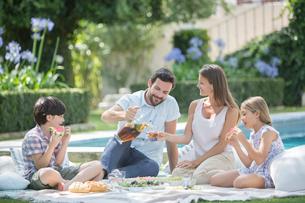 Family enjoying picnic at poolsideの写真素材 [FYI02156115]
